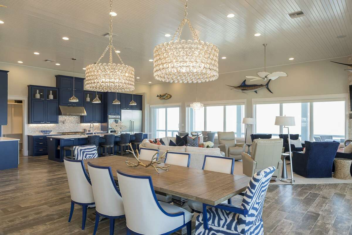 The home's great room has a dining area, card table, kichen and living room, with blue as a dominant color.