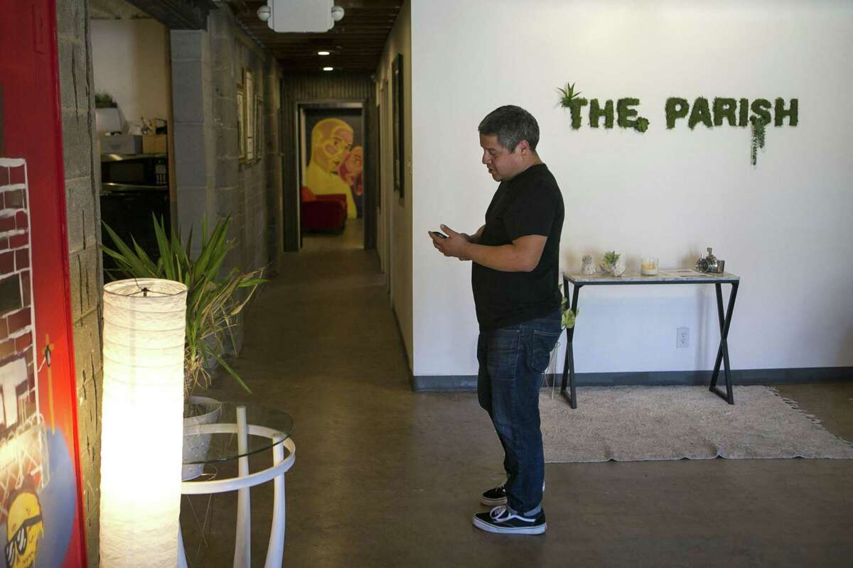 John Alexander Silvia checks his phone as he waits on a client at The Parish. In addition to the studios, there are several communal spaces where artists can relax, drink coffee, chat and bounce ideas off one another.