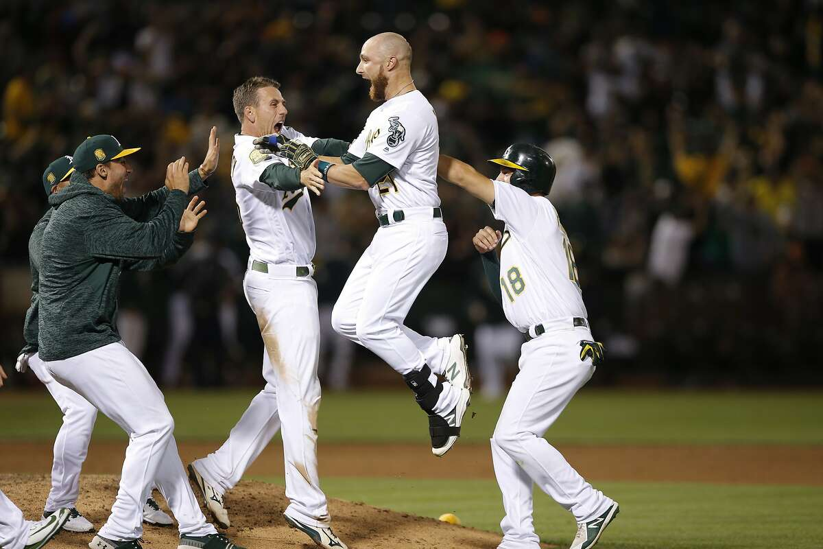 The Oakland Athletics celebrate with A's catcher Jonathan Lucroy (21) after he hit the game winning hit during the bottom of the 11th inning in an MLB game between the Oakland Athletics and San Francisco Giants at the Oakland Coliseum on Saturday, July 21, 2018, in Oakland, Calif. The A's won 4-3.