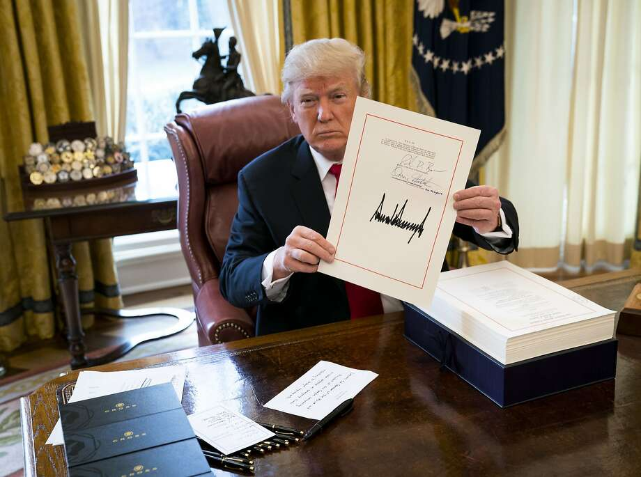 FILE — President Donald Trump signs tax legislation into law in the Oval Office, at the White House in Washington, Dec. 22, 2017. Photo: DOUG MILLS, NYT