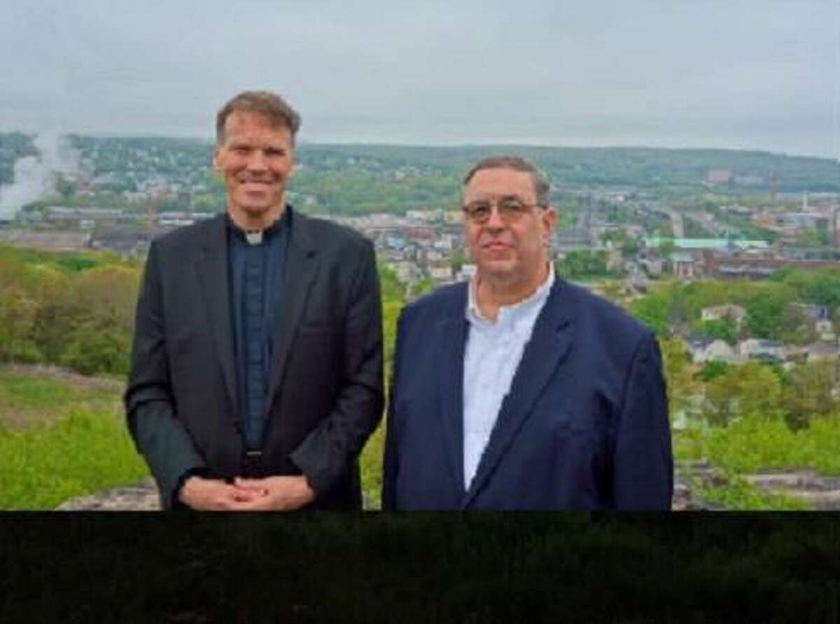 Father James Sullivan and Chuck Pagano, chairman of Holy Land USA, on the mountaintop overlooking the city of Waterbury
