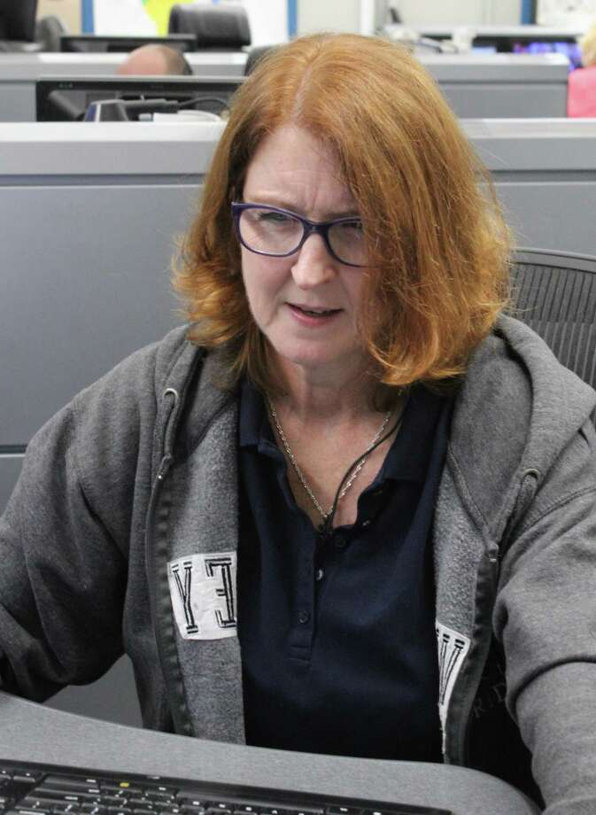 Lynn Erazmus takes a call in the town's Emergency Communications Center in Fairfield on Thursday. Photo: Genevieve Reilly / Hearst Connecticut Media / Fairfield Citizen
