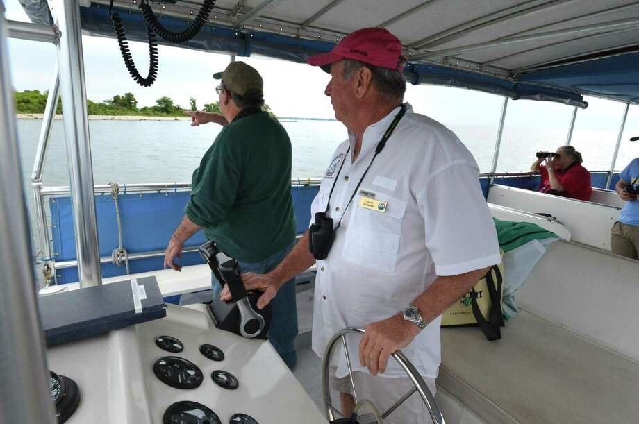 Above, Captain Al Kapuse keeps and eye out for shore birds during a bird-watching tour of Long Island Sound and the islands off the coast of Norwalk hosted by the Norwalk Seaport Association on June 10. Below, Norwalk's Cordelia Regan, right, and Ricardo Mendoza, center, look through binoculars at the birds. Above right, Peck Ledge Lighthouse. Photo: Alex Von Kleydorff / Hearst Connecticut Media / Norwalk Hour