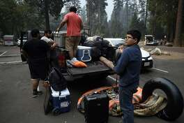 Marco Walker, red shirt, of Los Angeles packs up his extended family of 22, who were staying at historic Camp 4 in Yosemite National Park, on Wednesday, July 25, 2018. Walker and his family have been camping in the park for 17 years and this is the first time they have been evacuated. (Neal Waters/Zuma Press/TNS)