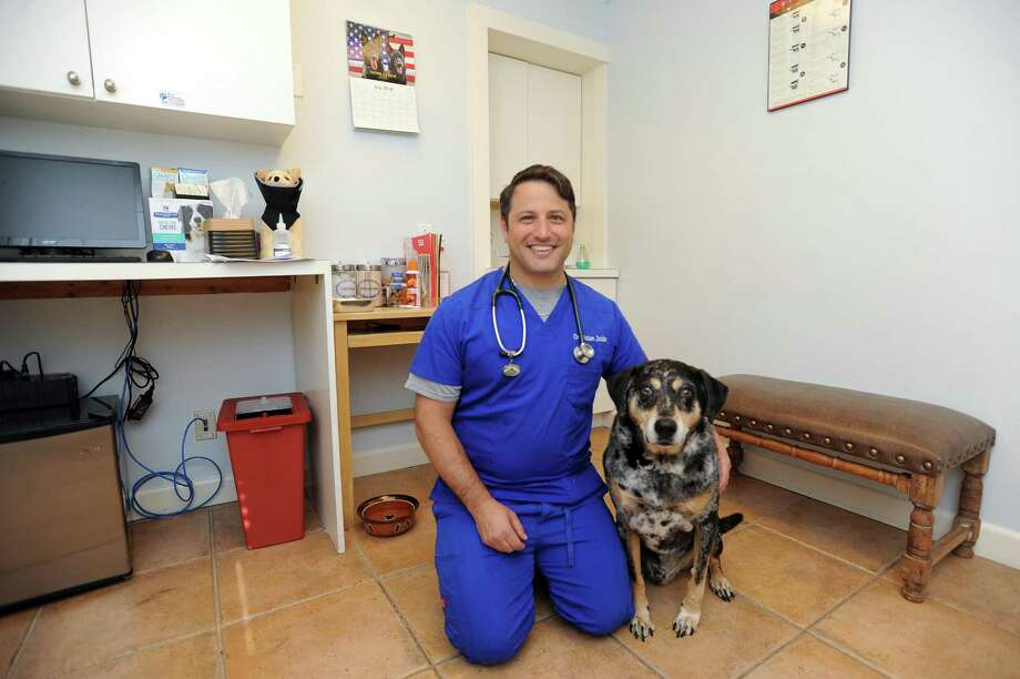 Dr. Nolan Zeide poses with his dog Vader inside an exam room at Bull's Head Animal Hospital on Long Ridge Rd. in Stamford, Conn. on Tuesday, July 24, 2018. New York City has seen a rise in dog flu cases recently, and the trend has been creeping up the coast into Fairfield County. Photo: Michael Cummo / Hearst Connecticut Media / Stamford Advocate