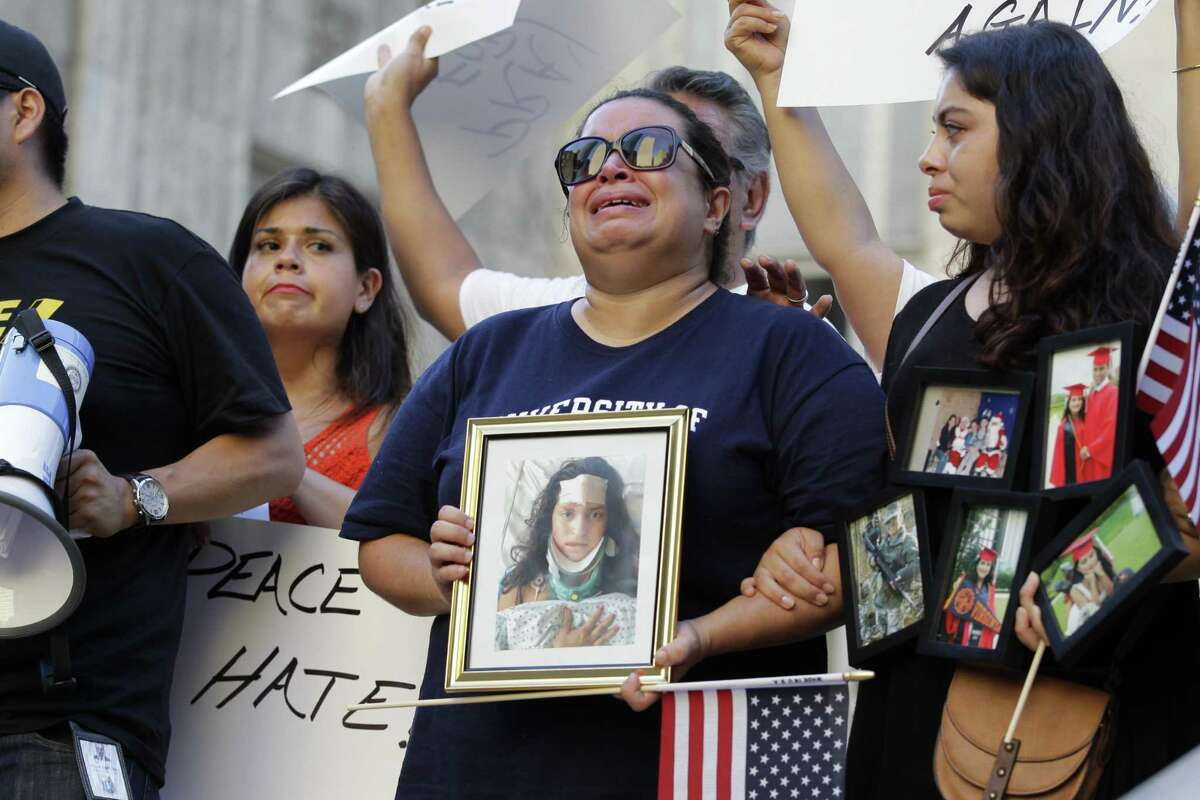Ericka Chaves cries as she holds a photo of her daughter Natalie Romero who was struck in Charlottesville as Houstonians held a vigil in solidarity with Charlottesville Anti-Racists at Houston City Hall Sunday, Aug. 13, 2017, in Houston. The rally was held to show show love, support, and solidarity for those killed and injured in a moving vehicle attack in Charlottesville Saturday.