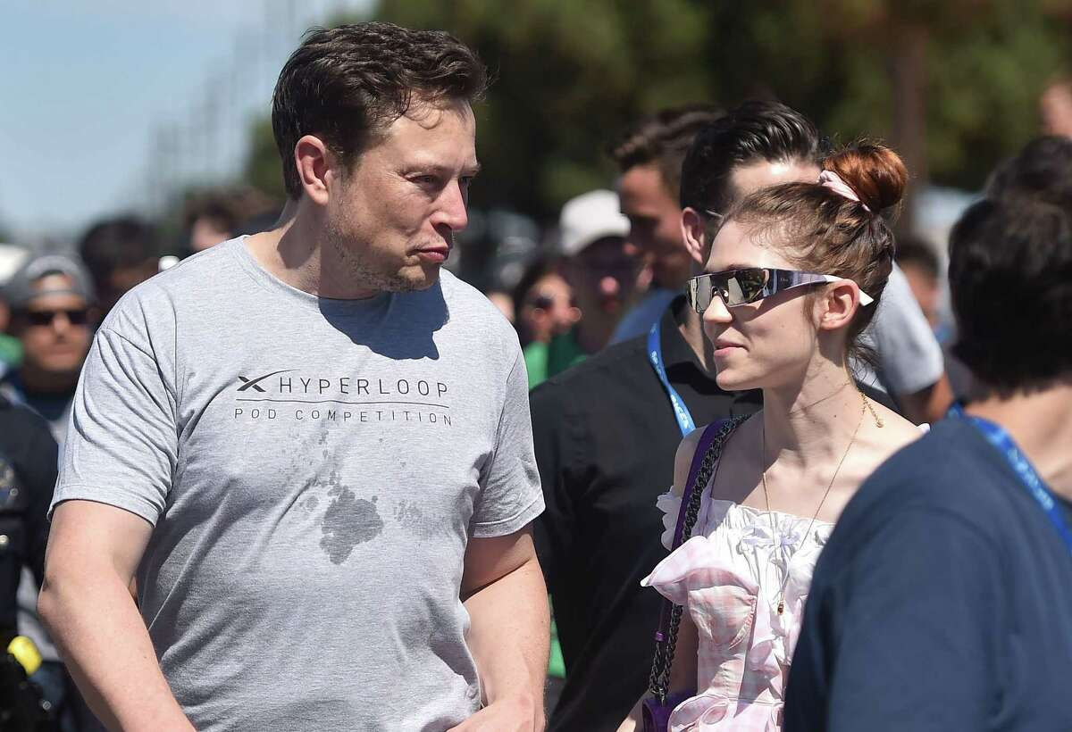 SpaxeX founder Elon Musk (L) and Canadian musician Grimes (Claire Boucher) attend the 2018 Space X Hyperloop Pod Competition, in Hawthorne, California on July 22, 2018. Students from colleges and universities from the US and around the world are taking part in testing their pods on a 1.25 kilometer-long (0.75-mile) tubular test track at the SpaceX headquarters. / AFP PHOTO / Robyn BeckROBYN BECK/AFP/Getty Images