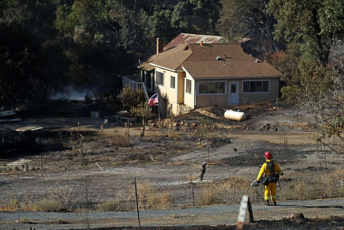 A CalFire firefighter looks at a house that was saved from the Marsh Fire in Clayton, Calif. on Thursday, July 26, 2018.