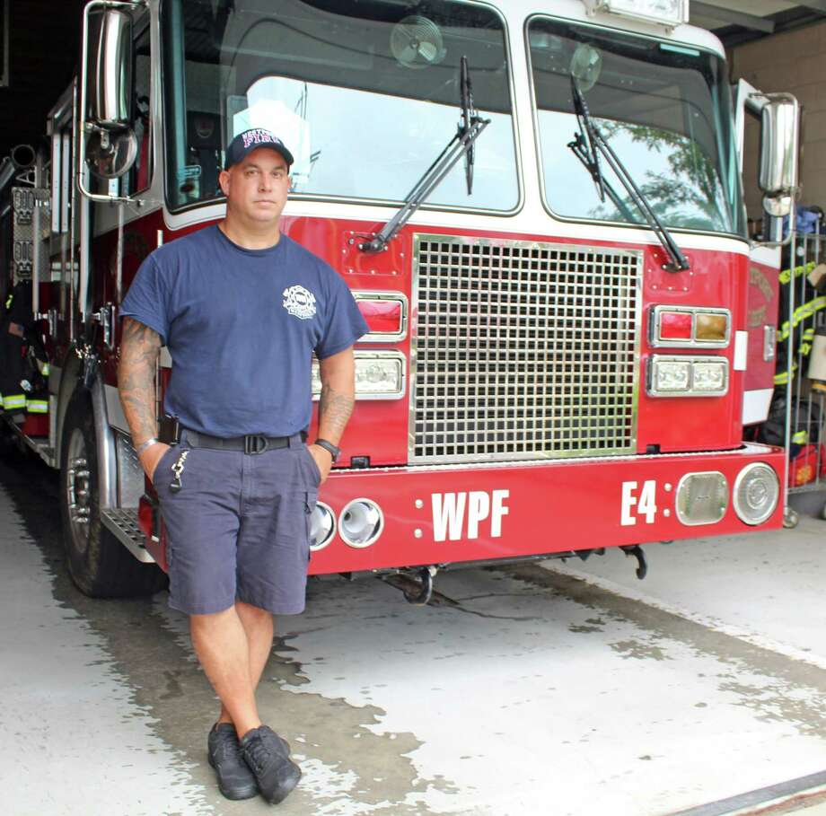 Nick Marsan, president of the Westport Uniformed Firefighters Association Local 1081, stands in front of fire engine number four at the Saugatuck firehouse on July 25. Photo: Sophie Vaughan / Hearst Connecticut Media / Westport News