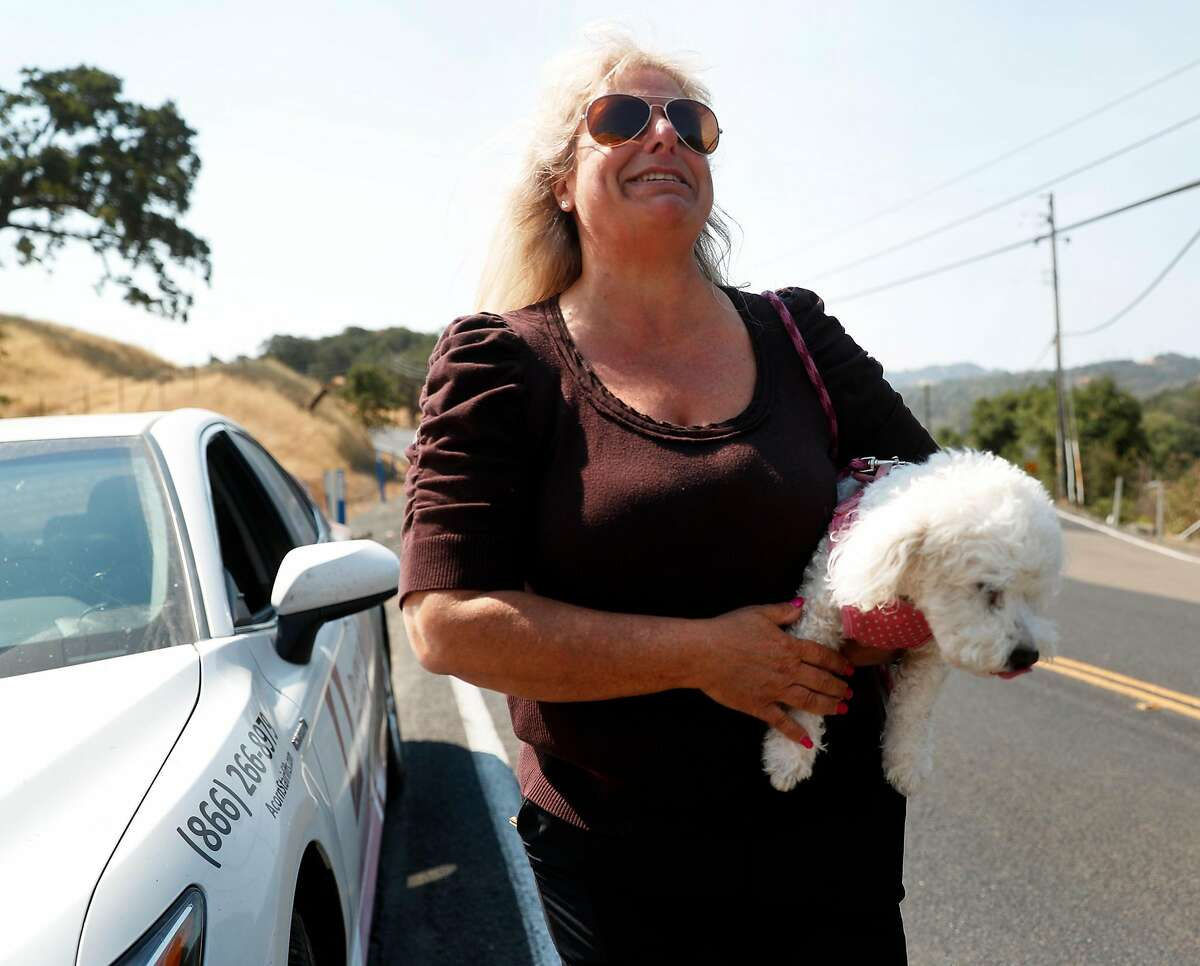 Kathy Neubecker reacts after being reunited with her dog, Molly Barker, at the Morgan Territory Road road block near the Marsh Fire in Clayton, Calif. on Thursday, July 26, 2018.