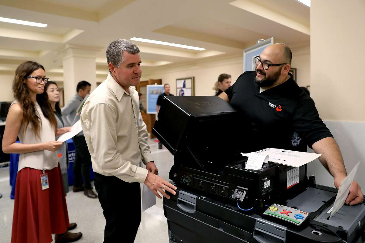 Department of Elections employees Iva Joy Maurin, left, and Inaki Fernandez de Retana listen to Jose Monroy, an employee with Dominion Voting Systems, during a demonstration of a new ballot-counting machine at San Francisco City Hall in San Francisco, Cali. on Wednesday, July 25, 2018.