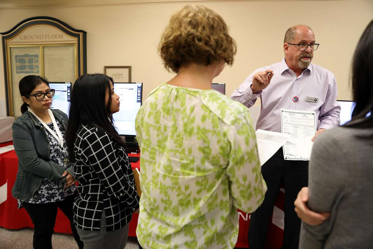 Larry Korb, an employee with Dominion Voting Systems, instructs employees with the Department of Elections about new ballot-counting machines at San Francisco City Hall in San Francisco, Cali. on Wednesday, July 25, 2018.