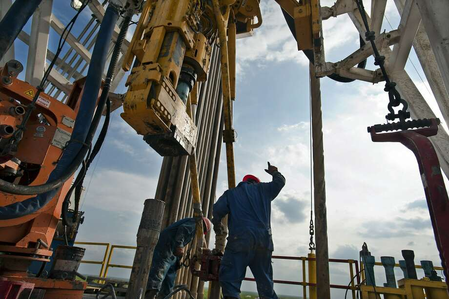 A floor hand signals to the driller to pull the pipe from the mouse hole on Orion Drilling Co.'s Perseus drilling rig near Encinal in Webb County, Texas, U.S., on Monday, March 26, 2012. Photo: Eddie Seal, Bloomberg