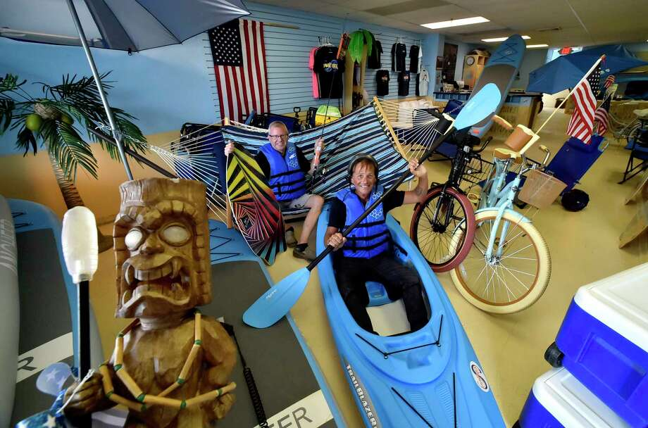 West Haven, Connecticut - Thursday,  July 26, 2018:  Kevin Darcey, left, and George Curtis, owners of the Savin Rock Surf Shop in West Haven, who have started West Haven's first beach equipment rental shop for West Haven beaches that include  safety equipment for bicycling and kayaking, rentals of paddle boards, boogie boards, skim boards, kayaks, bicycles, beach bicycles, coolers , hammocks umbrellas, canopies, tables, lounge chairs, beach cart carts that convert into chairs and a myriad of other fun gear made for enhancing the enjoyment of a fun day on the shoreline. They deliver the gear to the West Haven beach of your choice, set the gear up, and take it down. Their is also fishing gear and other beach items for sale for sale Photo: Peter Hvizdak, Hearst Connecticut Media / New Haven Register