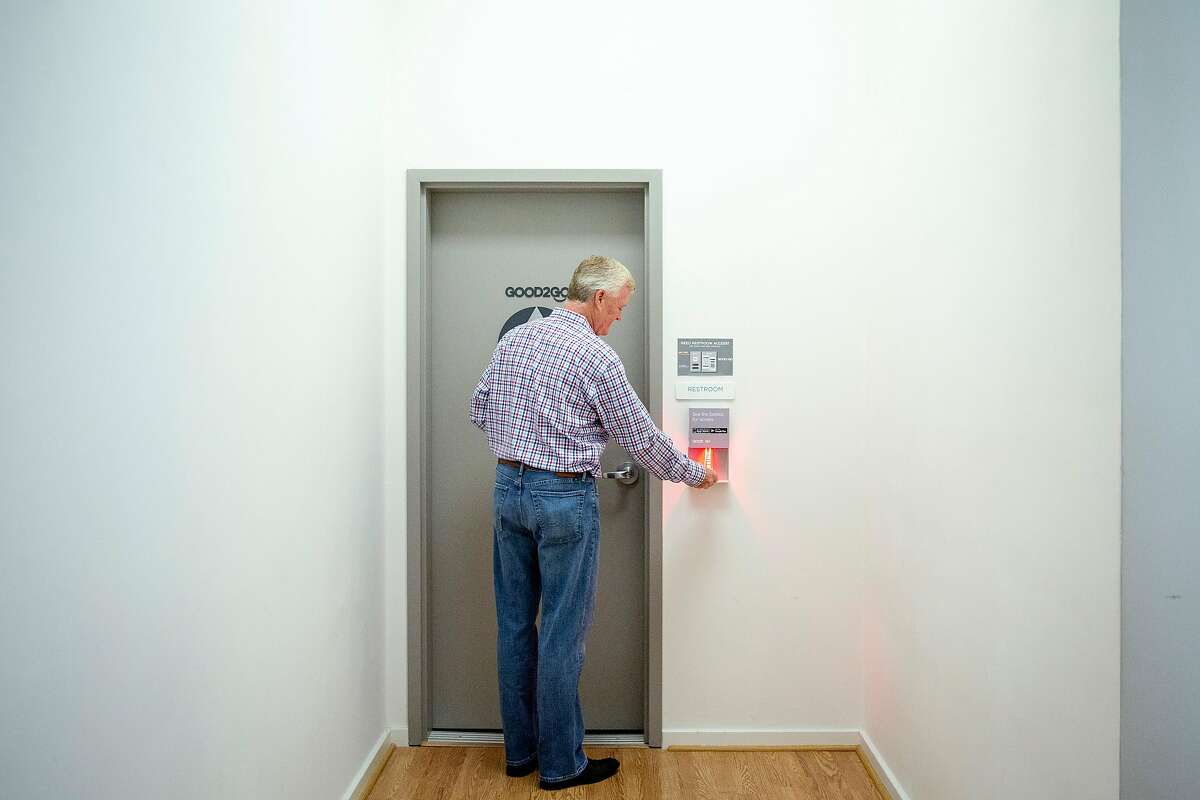 The Creamery's Ivor Bradley scans a barcode that automatically opens the door to the restroom after he was notified by an electronic display that he is next in line during a training session at the Good2Go headquarters, Thursday, July 26, 2018, in San Francisco, Calif. Good2Go is an app that grants users access to restrooms.