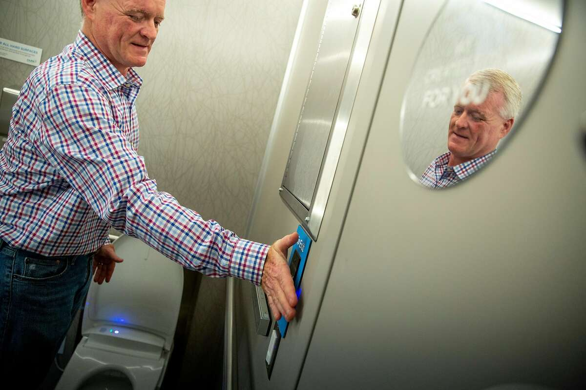 The Creamery's Ivor Bradley waves his hand at the touch-free sensor to exit the restroom during a training session at the Good2Go headquarters, Thursday, July 26, 2018, in San Francisco, Calif. Good2Go is an app that grants users access to restrooms.