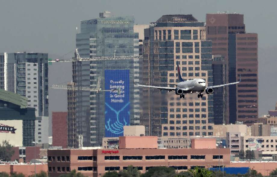 $85 roundtrip Oakland-Phoenix- Pictured: The downtown skyline as a jet lands at Sky Harbor airport Photo: Matt York, Associated Press