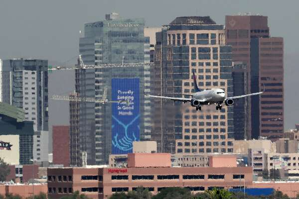 "In this Monday, July 23, 2018 photo, heat ripples blur the downtown skyline as a jet lands in Phoenix, Ariz., as temperatures exceed 100 degrees in the morning hours. Already devilishly hot for being in the Sonoran desert, Arizona's largest city is also an ""urban heat island,"" a phenomenon that pushes up temperatures in areas covered in heat-retaining asphalt and concrete. Phoenix officials say they are tackling urban warming, monitoring downtown temperatures, planting thousands of trees and capturing rainwater to cool off public spaces. (AP Photo/Matt York)"