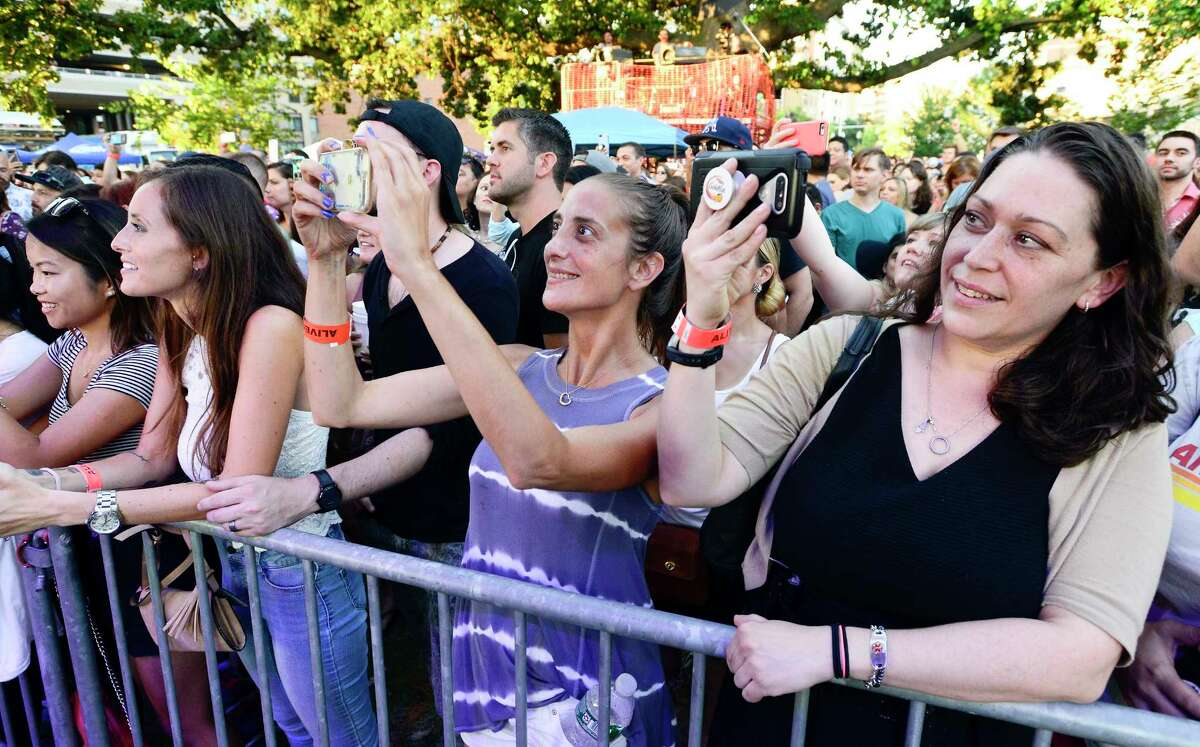 Sarah Cioffari of Greenwich, center, and friend Lilybet Karamaihah of Stamford, at right, capture the performance of Lifehouse during the Alive@Five concert series at Columbus Park on July 26, 2018 in Stamford, Connecticut.