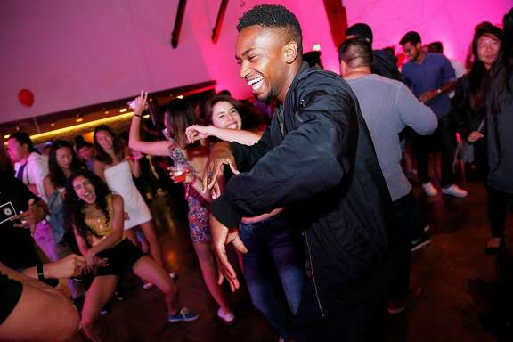 Brent Samuels, a software engineering intern at Facebook, dances among other interns during a Jumpstart launch party at the Pearl venue on Friday, July 20, 2018, in San Francisco, Calif. Jumpstart celebrated the release of their AI-powered recruiting app.