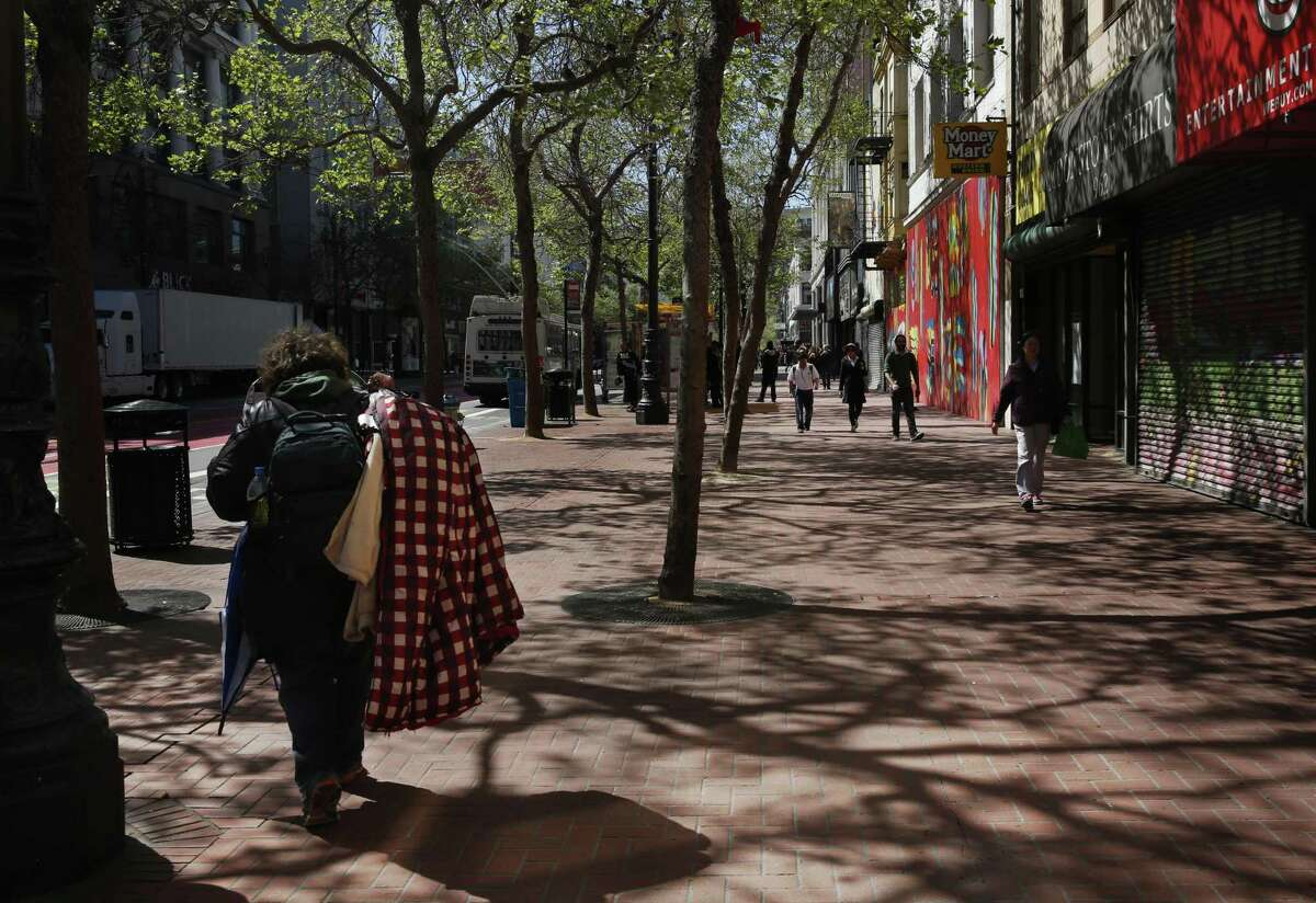 A person heads down Market street carrying blankets and other belongings. Businesses in the area are struggling with the misery on the city's streets.
