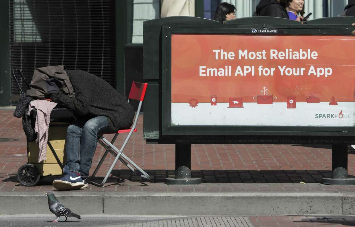 A man sleeps on a chair on Market Street, where many businesses are struggling as the street population grows.