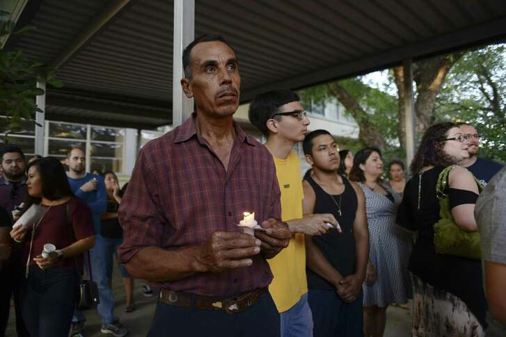 Victor Hernandez holds a candle during a July gathering to remember William Davis, technology teacher at Rhodes Middle School, who died in Uganda.