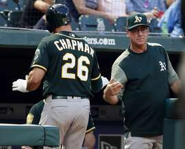 Oakland Athletics' Matt Chapman (26) is congratulated by manager Bob Melvin (6) after Chapman scored against the Texas Rangers during the fourth inning of a baseball game Thursday, July 26, 2018, in Arlington, Texas. (AP Photo/Michael Ainsworth)