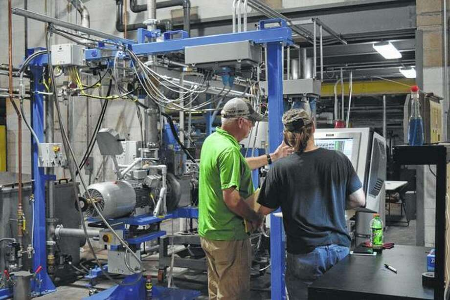 Mike Krause (left), general manager of BPC LLC-Toll Compounding and Blending, talks with BPC senior operator Pat Reed of Meredosia at the Meredosia plastics plant's new extrusion line. Photo:       Greg Olson | Journal-Courier
