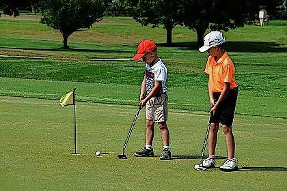 Logan Bryant, 5, and Brayden Byers, 7, both of Jacksonville practice on the putting green Thursday. Photo:       Audrey Clayton | Journal-Courier