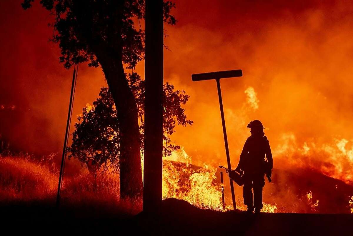 A firefighter lights backfires during the Carr fire in Redding, California on July 27, 2018. One firefighter has died and at least two others have been injured as wind-whipped flames tore through the region. One person has died and at least two others have been injured as wind-whipped flames tore through the region.