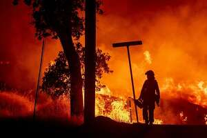 TOPSHOT - A firefighter lights backfires during the Carr fire in Redding, California on July 27, 2018. One firefighter has died and at least two others have been injured as wind-whipped flames tore through the region.  One person has died and at least two others have been injured as wind-whipped flames tore through the region.  / AFP PHOTO / JOSH EDELSONJOSH EDELSON/AFP/Getty Images