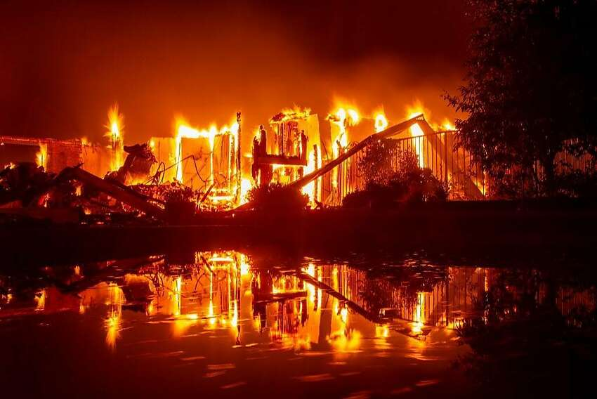 A burning home is reflected in a pool during the Carr fire in Redding, California on July 27, 2018. One firefighter has died and at least two others have been injured as wind-whipped flames tore through the region.