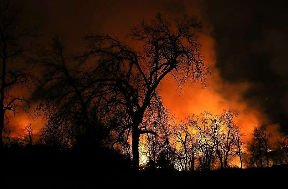 REDDING, CA - JULY 27:  An orange glow from the Carr Fire lights up burnt trees as the fire burns through dry brush on July 27, 2018 in Redding, California. A firefighter was killed battling the fast moving Carr Fire which has burned over 28,000 acres and destroyed dozens of homes. The fire is reportedly only 6 percent contained.  (Photo by Justin Sullivan/Getty Images) Photo: Justin Sullivan, Getty Images