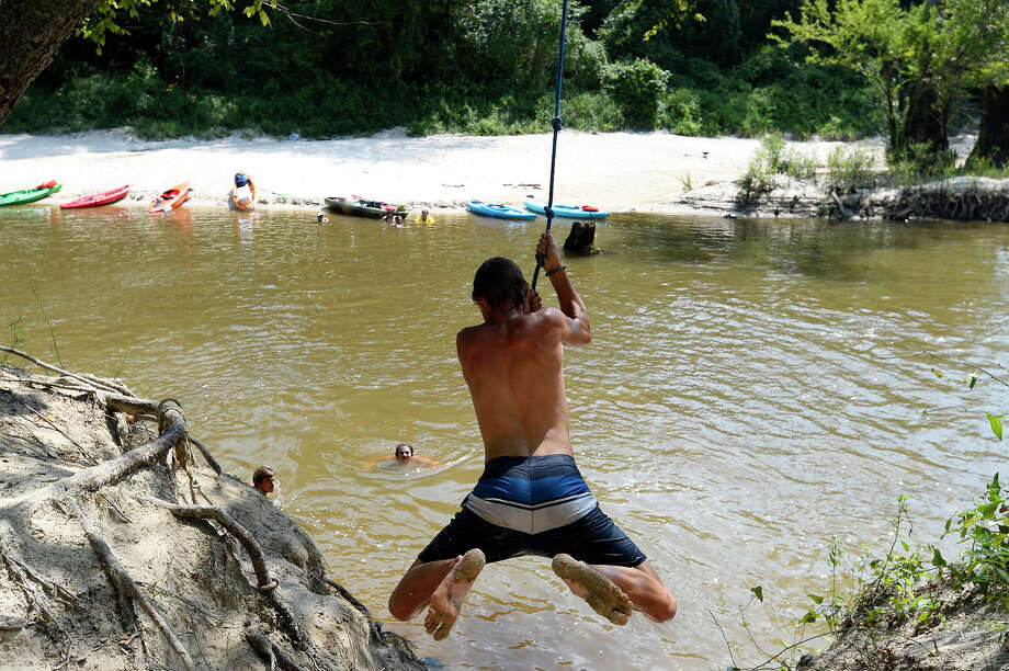 Zach Busby, 16, swings into the water near Baby Galvez Landing on Village Creek.  Photo taken Wednesday 7/25/18 Ryan Pelham/The Enterprise Photo: Ryan Pelham/The Enterprise / ?2018 The Beaumont Enterprise