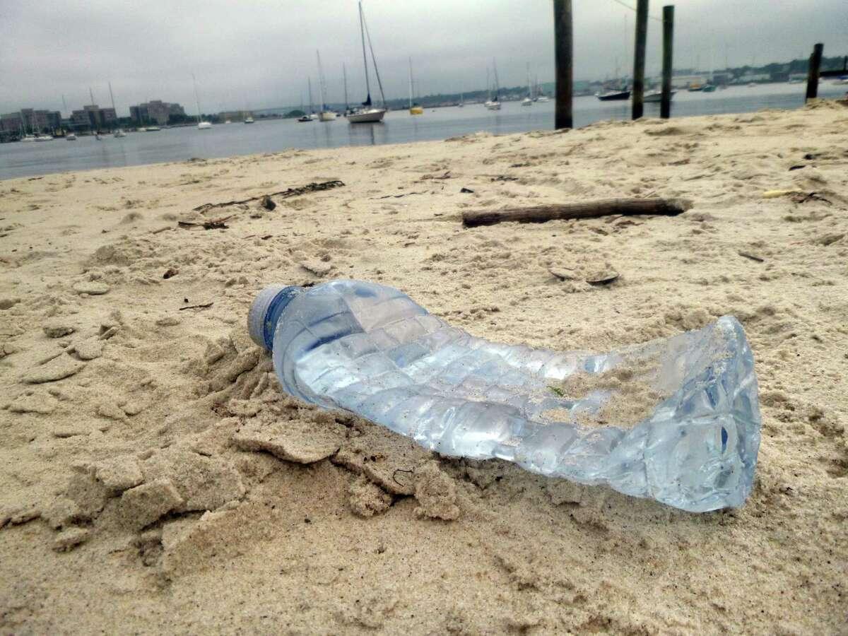 An empty plastic water bottle lies on a Long Island Sound beach.