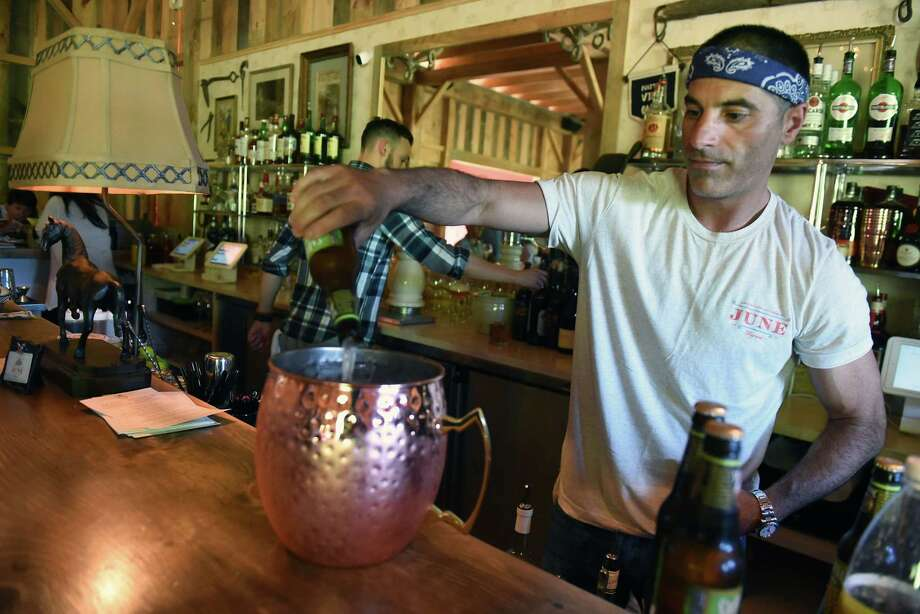 Owner Matt Baumgartner pours a birthday mule drink in the Pony Barn cocktail lounge and restaurant at June Farms on Wednesday, July 18, 2018 in West Sand Lake, N.Y. (Lori Van Buren/Times Union) Photo: Lori Van Buren / 20044359A