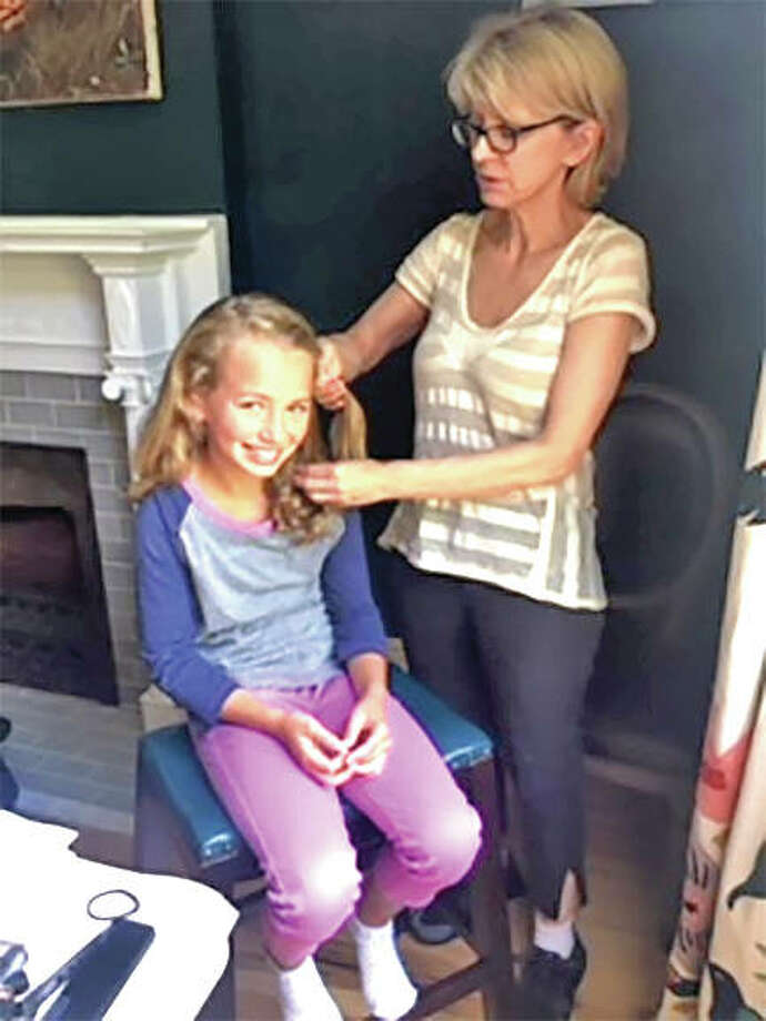 Mia Diltz, 9, of Edwardsville, has her hair combed by makeup artist Priscilla Case during a recent photo shoot for an Amazon Prime Day commercial. Photo:     For The Intelligencer