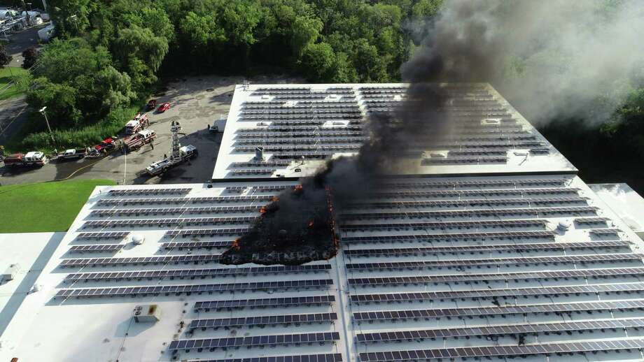 A roof-top solar panel array caught fire Thursday evening in southern Danbury, sending plumes of thick black smoke into the air that were visible for miles. Photo: / Rob Fish
