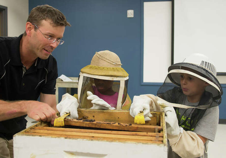 SIUE's Jake Williams, PhD, educates Odyssey Science Camp students Theresa Iwayemi (middle) and Rhett Morris (right) on honeybees. Photo:       For The Telegraph
