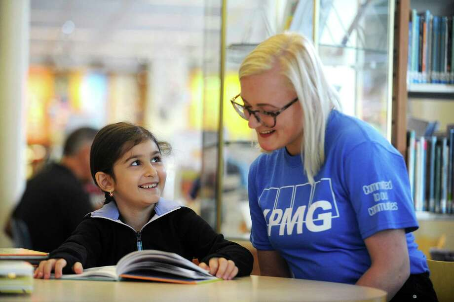 KPMG intern Michelle De Vries and six-year-old Mariam Chkhikvadze smile while reading together during Book Buddies inside the main branch of the Ferguson Library in downtown Stamford, Conn. on Thursday, July 26, 2018. Photo: Michael Cummo / Hearst Connecticut Media / Stamford Advocate