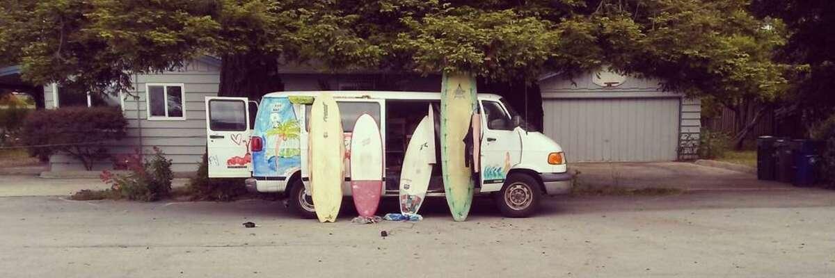 Surf boards leaning against Bodhi Goncharoff's van.