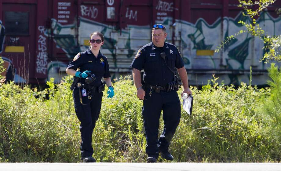 Investigators with the Montgomery County Sheriff's Office work the scene after a train near the intersection of Hanna Road and Robinson Road on Friday, July 27, 2018, in Oak Ridge, fatally struck a man. Photo: Jason Fochtman/Houston Chronicle