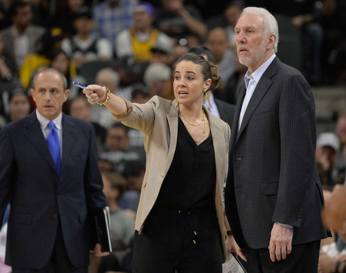 San Antonio Spurs assistant coach Becky Hammon talks to Spurs head coach Gregg Popovich, right, on the court during a timeout in the second half of an NBA basketball game against the Los Angeles Lakers, Saturday, Feb. 6, 2016, in San Antonio. San Antonio won 106-102. (AP Photo/Darren Abate)
