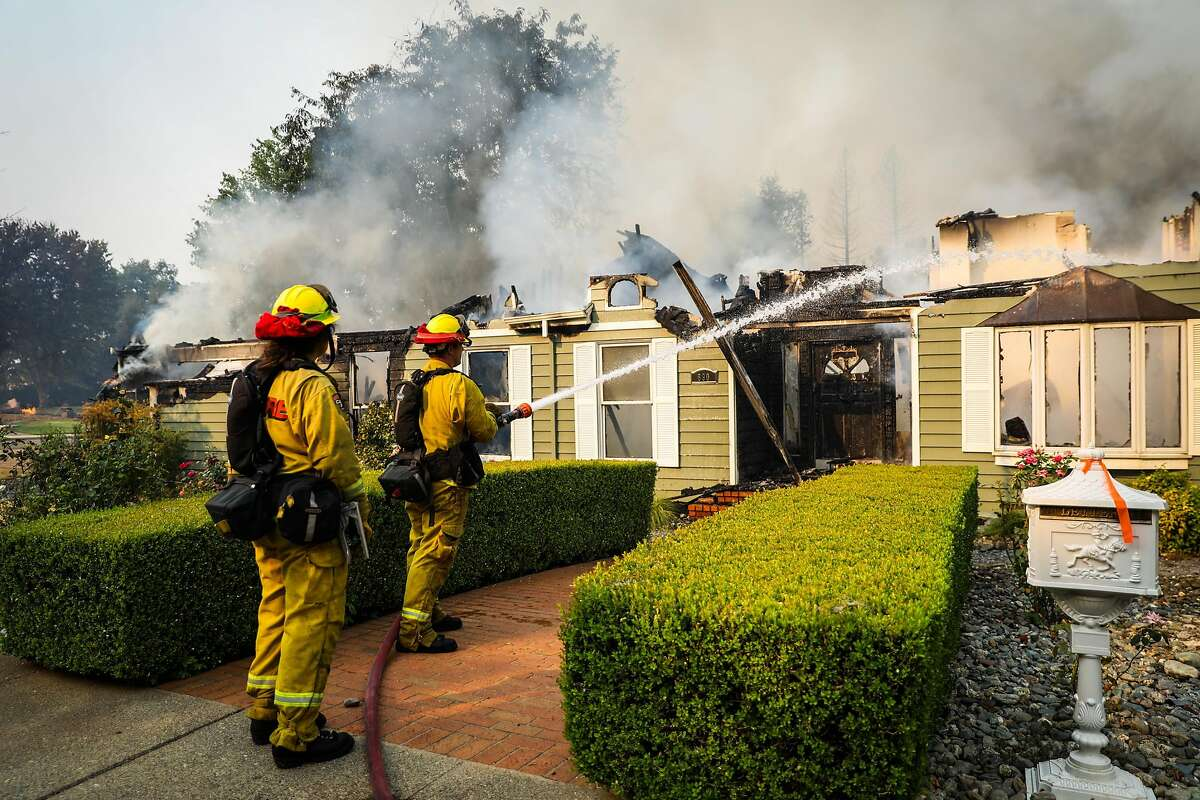 Firefighters work on a burning house on Sunriver Lane during the Carr Fire in Redding, California, on Friday, July 27th, 2018.