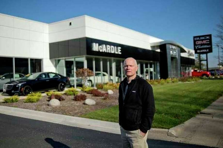 Tom McArdle, current owner of McArdle Buick GMC Cadillac, stands in front of the auto dealership. On Tuesday, the business will be sold to Betten Baker Auto Group. (File photo)