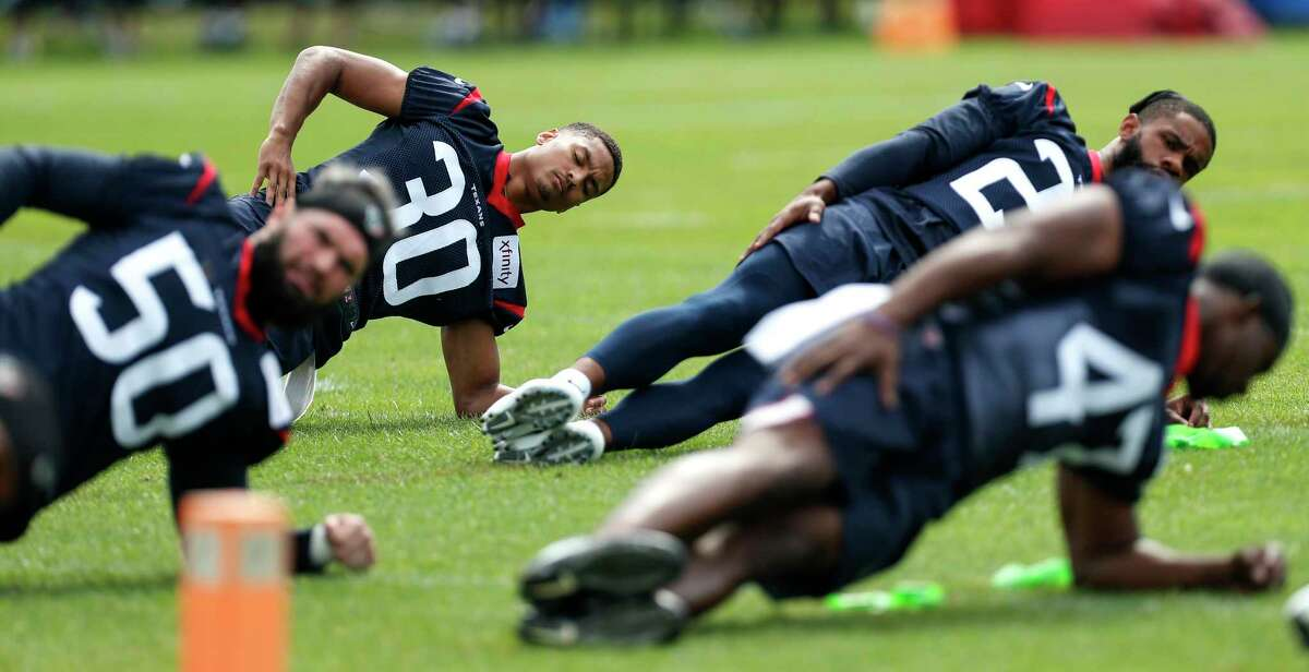 Houston Texans cornerback Kevin Johnson (30) and linebacker Ben Heeney (50) stretch during training camp at the Greenbrier Sports Performance Center on Friday, July 27, 2018, in White Sulphur Springs, W.Va.