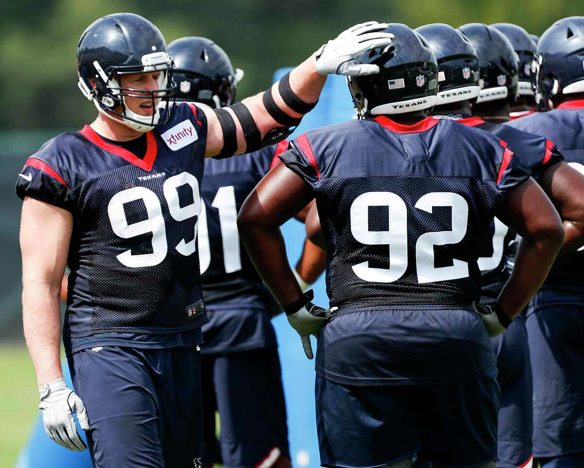 Houston Texans defensive end J.J. Watt (99) taps defensive tackle Brandon Dunn (92) on the helmet as they run drills during training camp at the Greenbrier Sports Performance Center on Friday, July 27, 2018, in White Sulphur Springs, W.Va.
