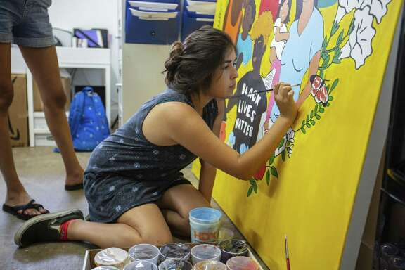 Volunteer Adrienne Sanchez, 20, helps paint a mural that was designed by artist Jocelyn Riojas for the NAACP National convention which will hang at St. Philip's College in San Antonio on July 24, 2018 in Austin, Texas.