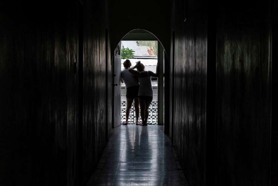 "Luz, left, and another Venezuelan woman are victims of sex trafficking in Trinidad. The women are now staying in a safe house with the help of a nonprofit. ""We are helpless. All because of the crisis,"" Luz said. Photo: Washington Post Photo By Jahi Chikwendiu. / The Washington Post"